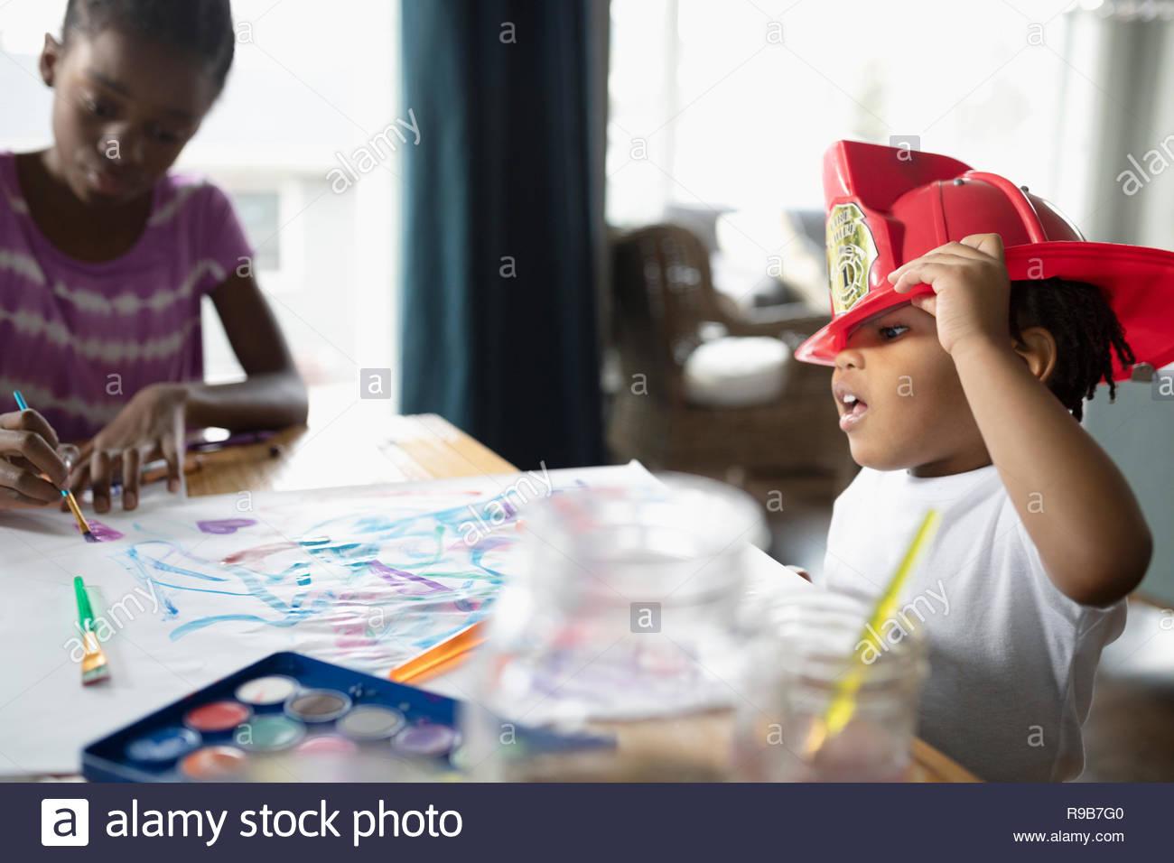 Lindo niño niño usando casco de bombero y pintura en mesa de comedor Imagen De Stock