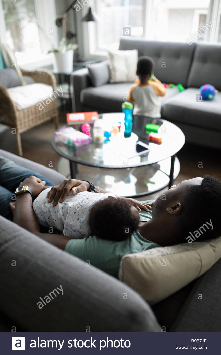 Cansado padre con hijo durmiendo en el sofá de la sala Imagen De Stock
