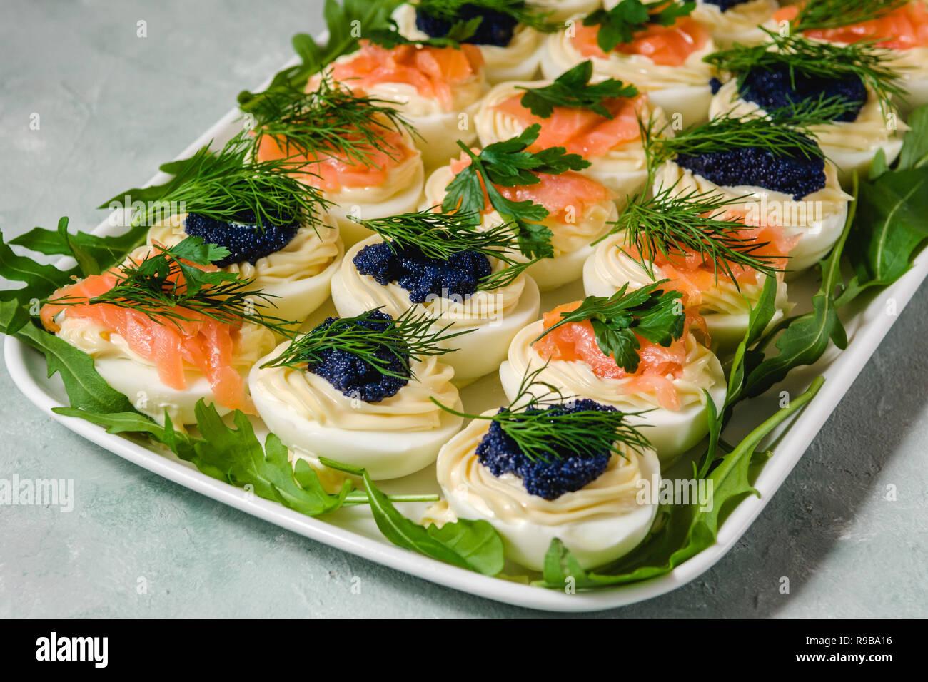Huevos rellenos con salmón y caviar decorado con perejil y eneldo. Parte alimentos Foto de stock