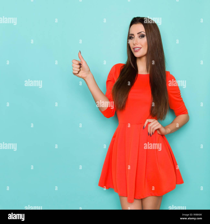 8c74efbe7 Seguros de bella mujer en mini vestido rojo está mostrando el pulgar hacia  arriba. Tres cuartos de longitud foto de estudio sobre fondo turquesa.