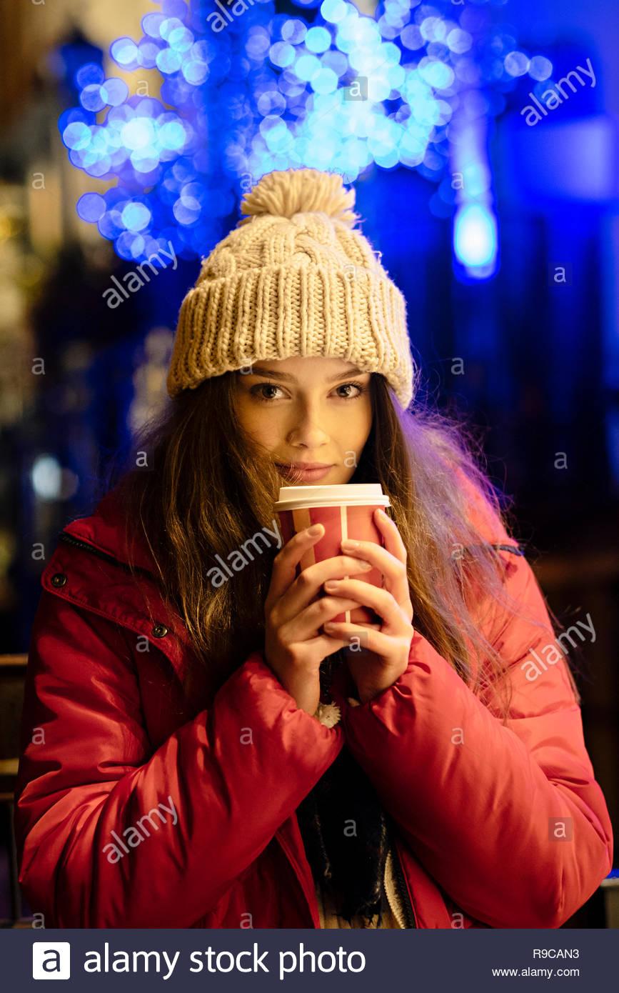 Niña de sombrero de lana blanca y chaqueta roja bebiendo chocolate caliente  en invierno con las 912fe80930e