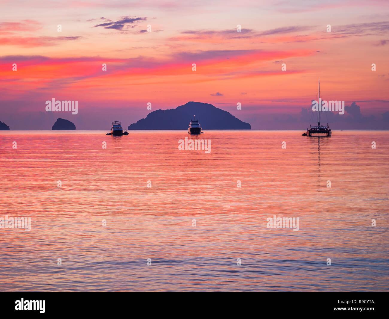 Tres barcos amarrados en la bahía tranquila al atardecer, cielo rojo, tranquilo, perfecto para el fondo de la escena Foto de stock
