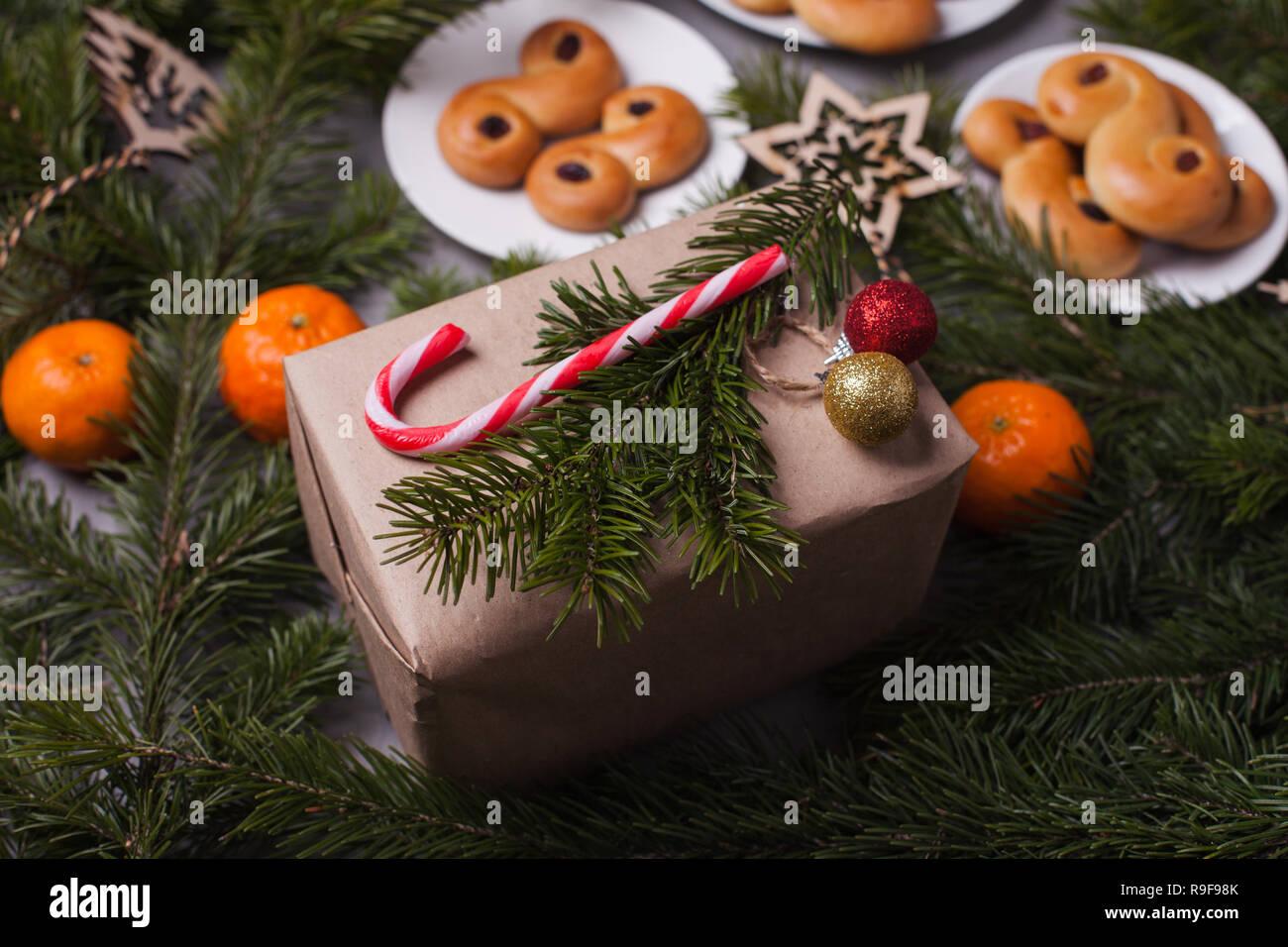 Azafrán Buns tradicionales suecos, también conocido como o lussebullar lussekatter. Los bollos de amarillo tiene pasas y tienen forma de espirales y caja de regalo xcon Foto de stock