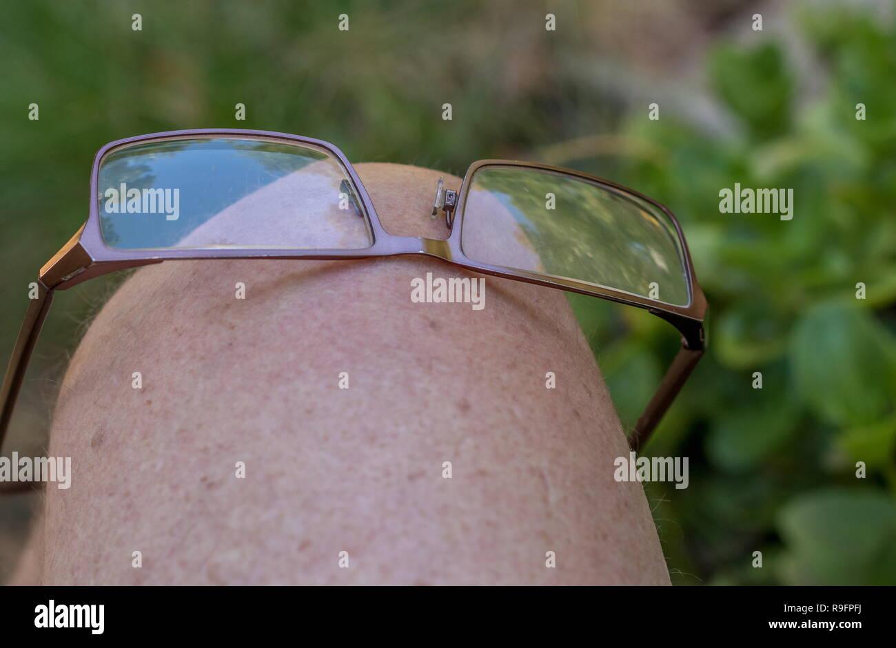 Gafas de lectura equilibrada en una rodilla caucásica,imagen con copia espacio en formato horizontal Imagen De Stock