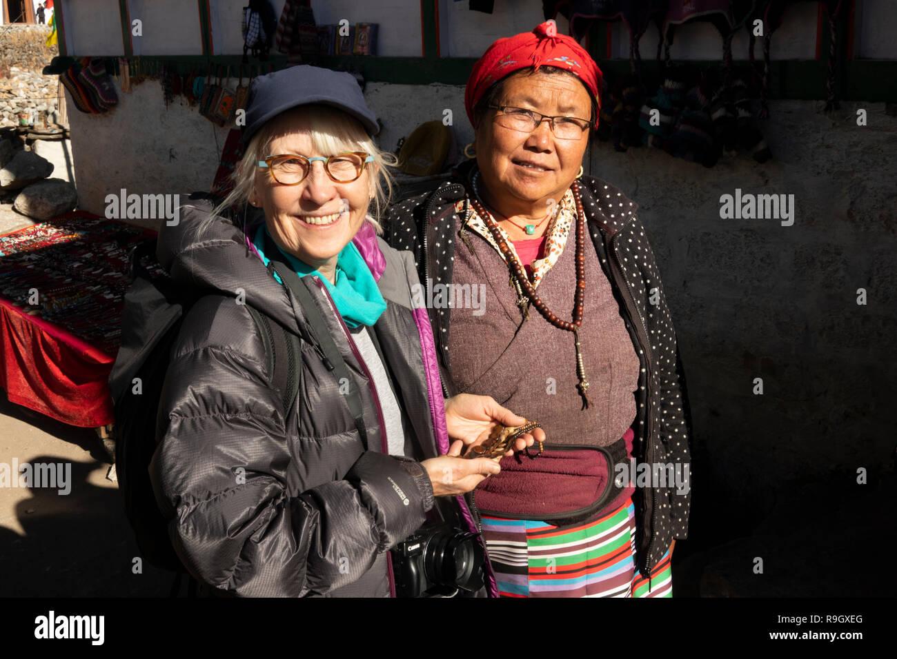 Np950, Nepal, el campamento base del Everest Trek, aldea de Khumjung, caminante con mujer local en la pequeña cala de recuerdo para turistas en camino a la aldea gompa Imagen De Stock