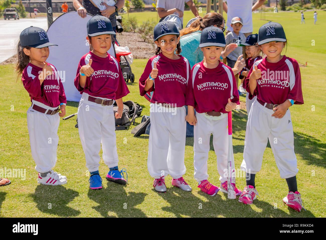 370bfed8becac Hispana y asiática americana de 4 años en las niñas de Little League  uniformes posan para