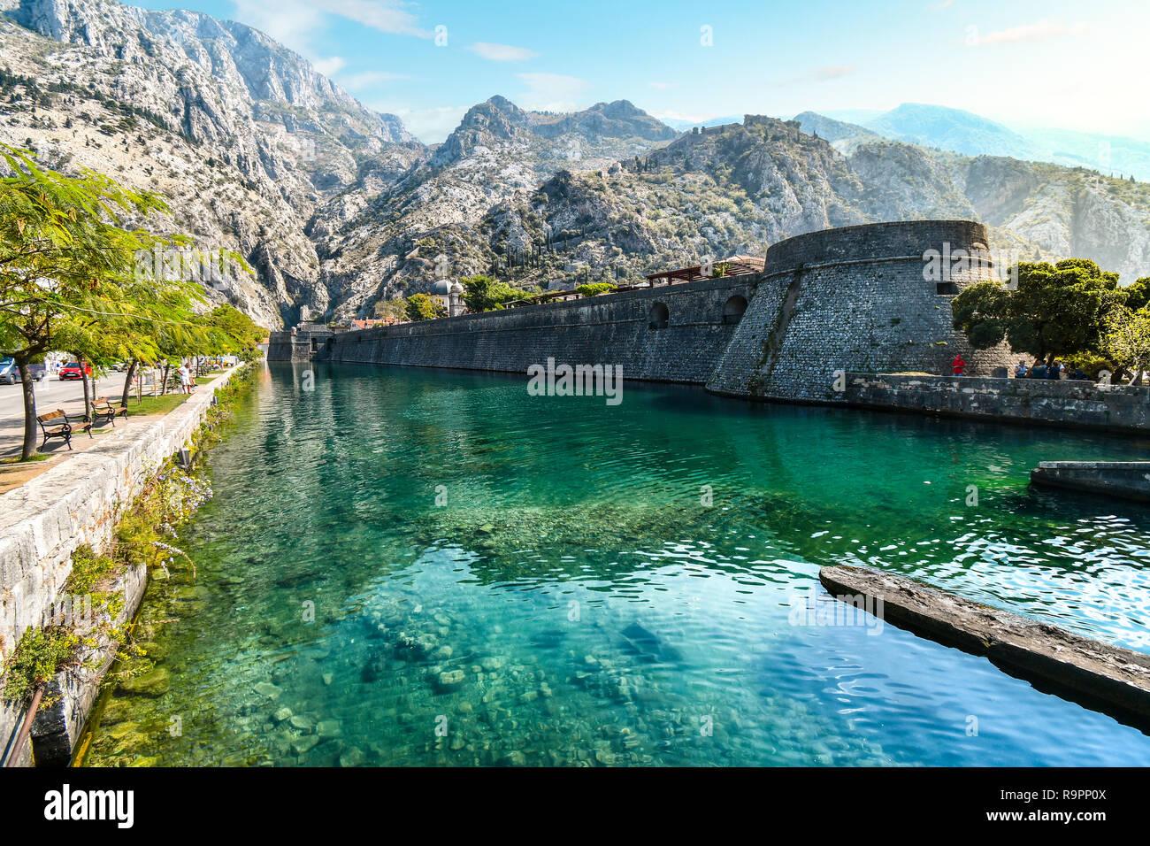 Las murallas medievales de la ciudad y el foso que separa a las montañas y el castillo detrás en el Adriático, antigua ciudad de Kotor, Montenegro. Foto de stock