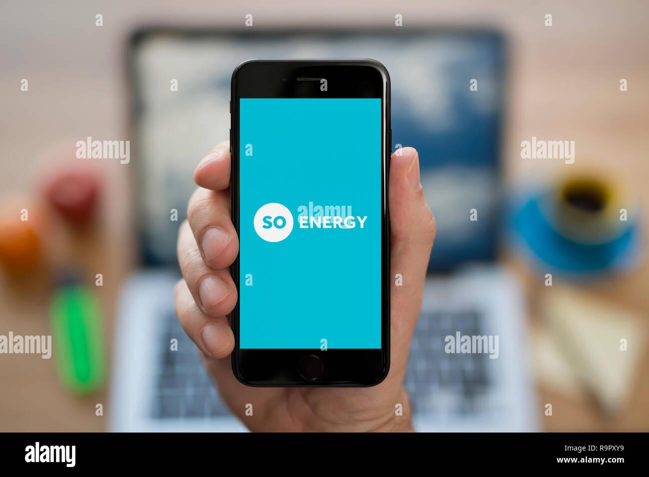 Un hombre mira su iPhone que muestra el logotipo de Energía (uso Editorial solamente). Imagen De Stock