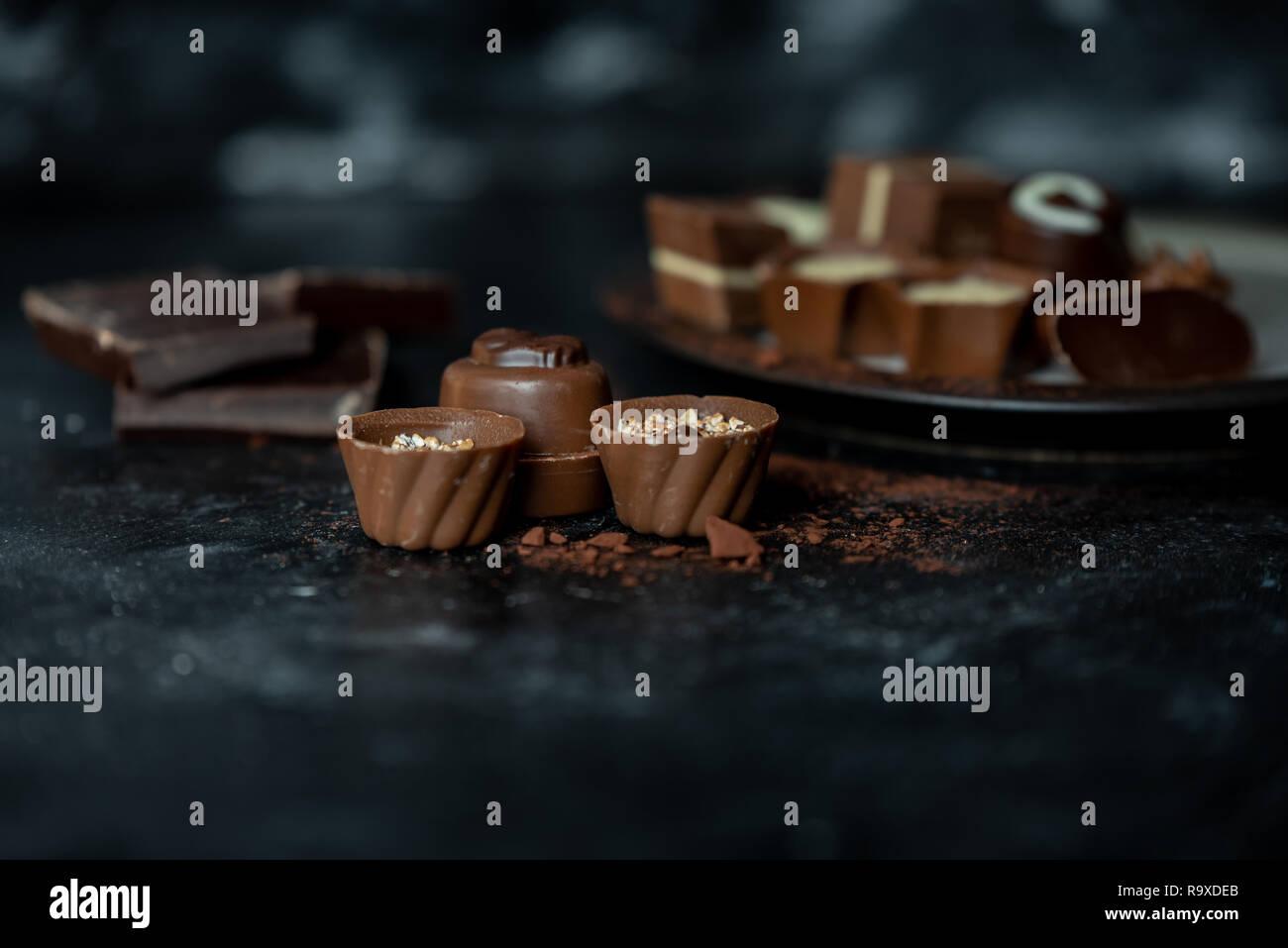 Diferentes pralines, dulce de leche, oscuro y chocolate blanco sobre un fondo oscuro, de madera Foto de stock