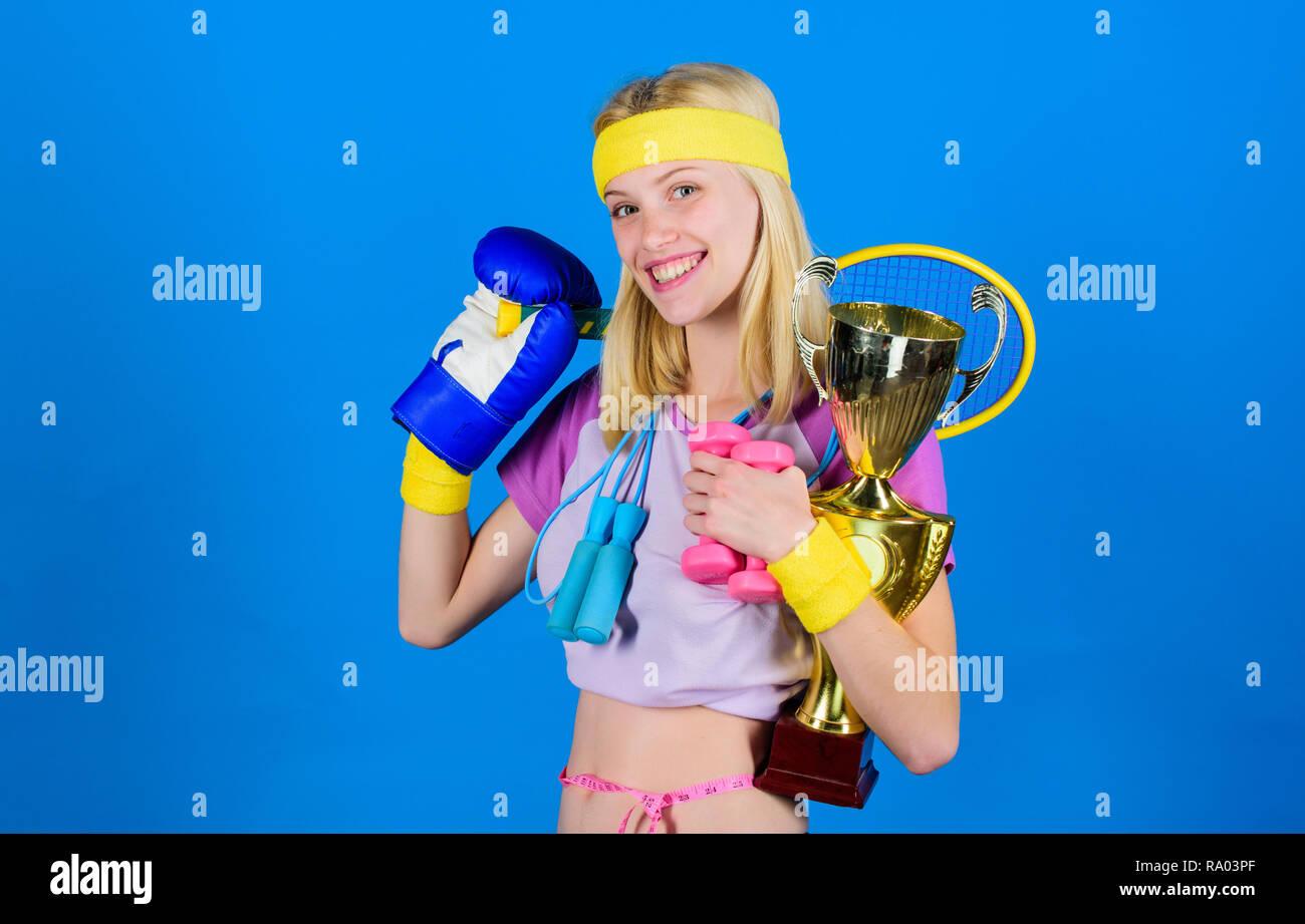 Sport Shop surtido. Chica exitosa mujer moderna de sostener el cáliz de oro y el equipo campeón deportivo fondo azul. Cómo encontrar tiempo para todo. Tienda de equipamiento deportivo. El deporte para todos los días. Imagen De Stock