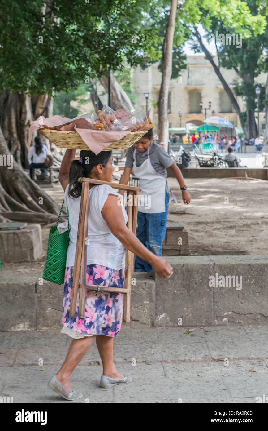 Mujeres que caminan con el canasto en la cabeza, en el zócalo, Oaxaca, México Imagen De Stock