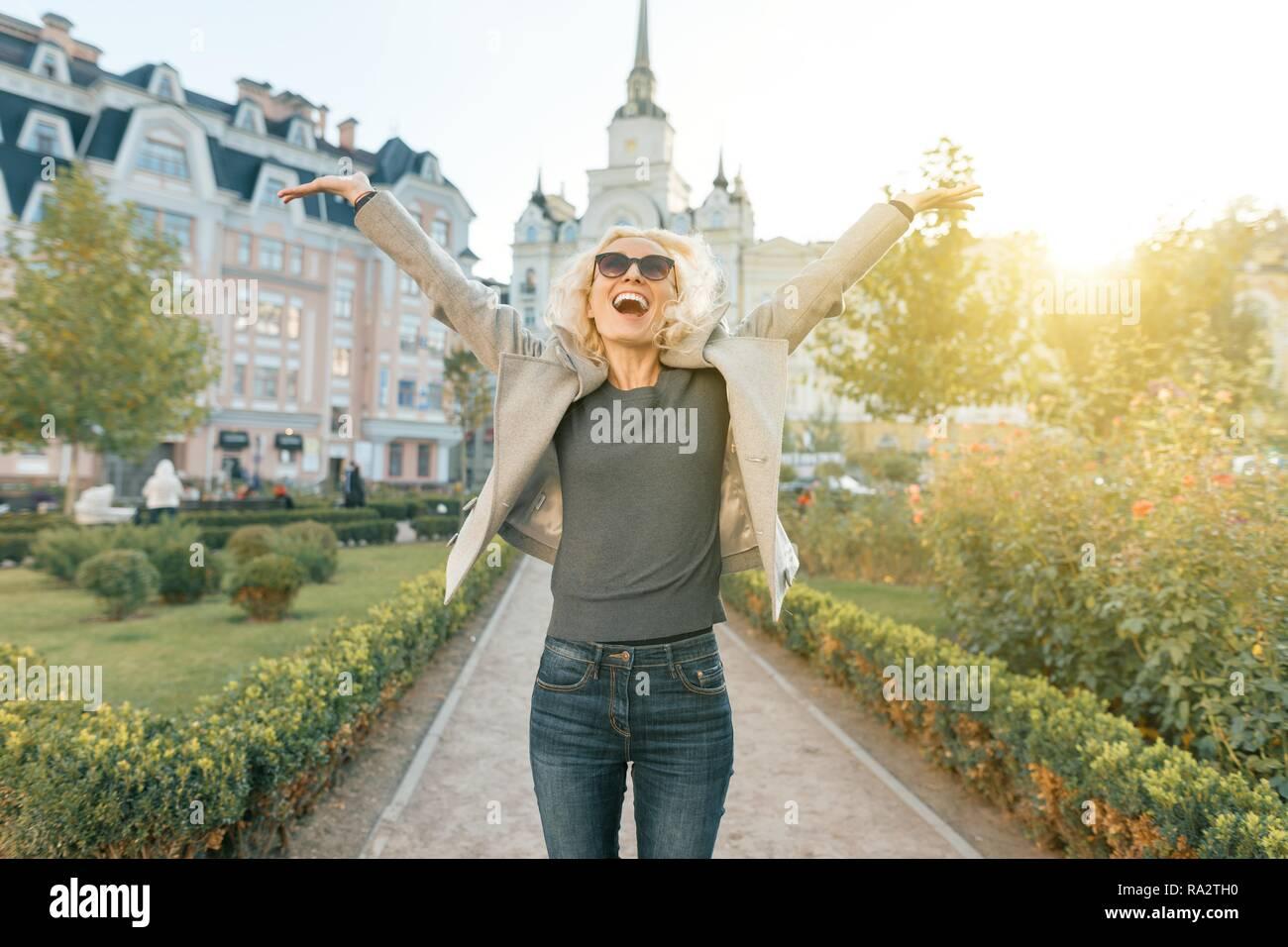 La emoción de alegría y felicidad, joven mujer alegre y levantó sus manos hacia arriba, en el exterior, fondo hora dorada. Foto de stock