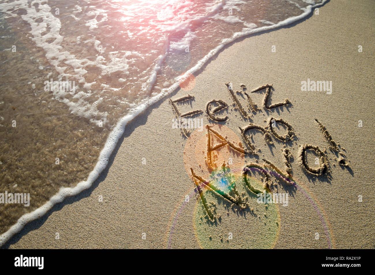 Portugués Feliz Ano Novo (Feliz año nuevo) mensaje escrito con letras con textura de arena fina con una nueva ola en una playa brasileña Imagen De Stock