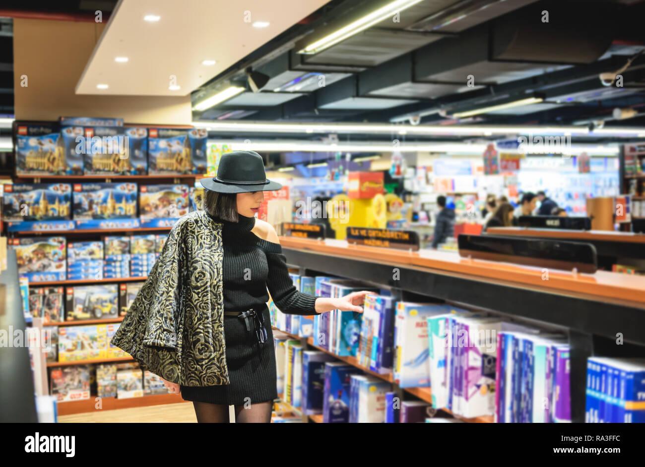 Atractiva mujer hermosa con traje y sombrero negro busca libros en librería  para comprar. 048718129a29