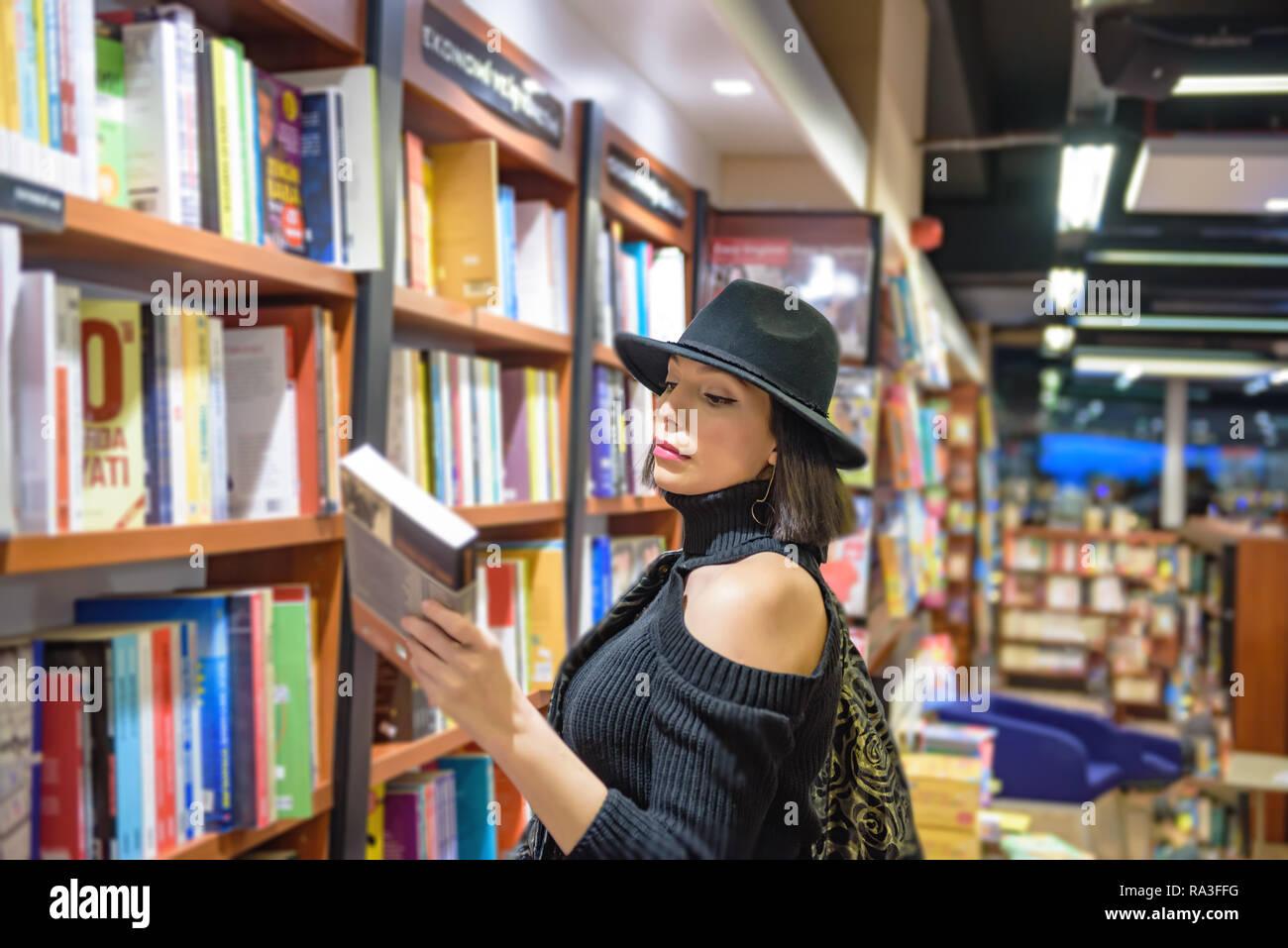 Atractiva mujer hermosa con traje y sombrero negro busca libros en librería  para comprar. Imagen 27446a1ebd06
