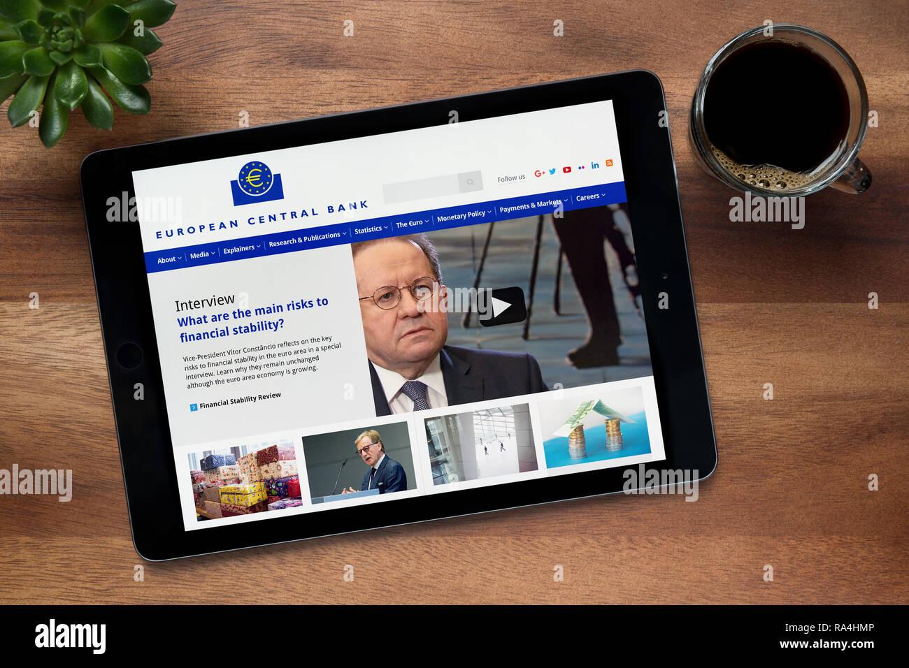 El sitio web del Banco Central Europeo se ha visto en un iPad, en una mesa de madera junto con un café espresso y una planta de casa (uso Editorial solamente) Foto de stock