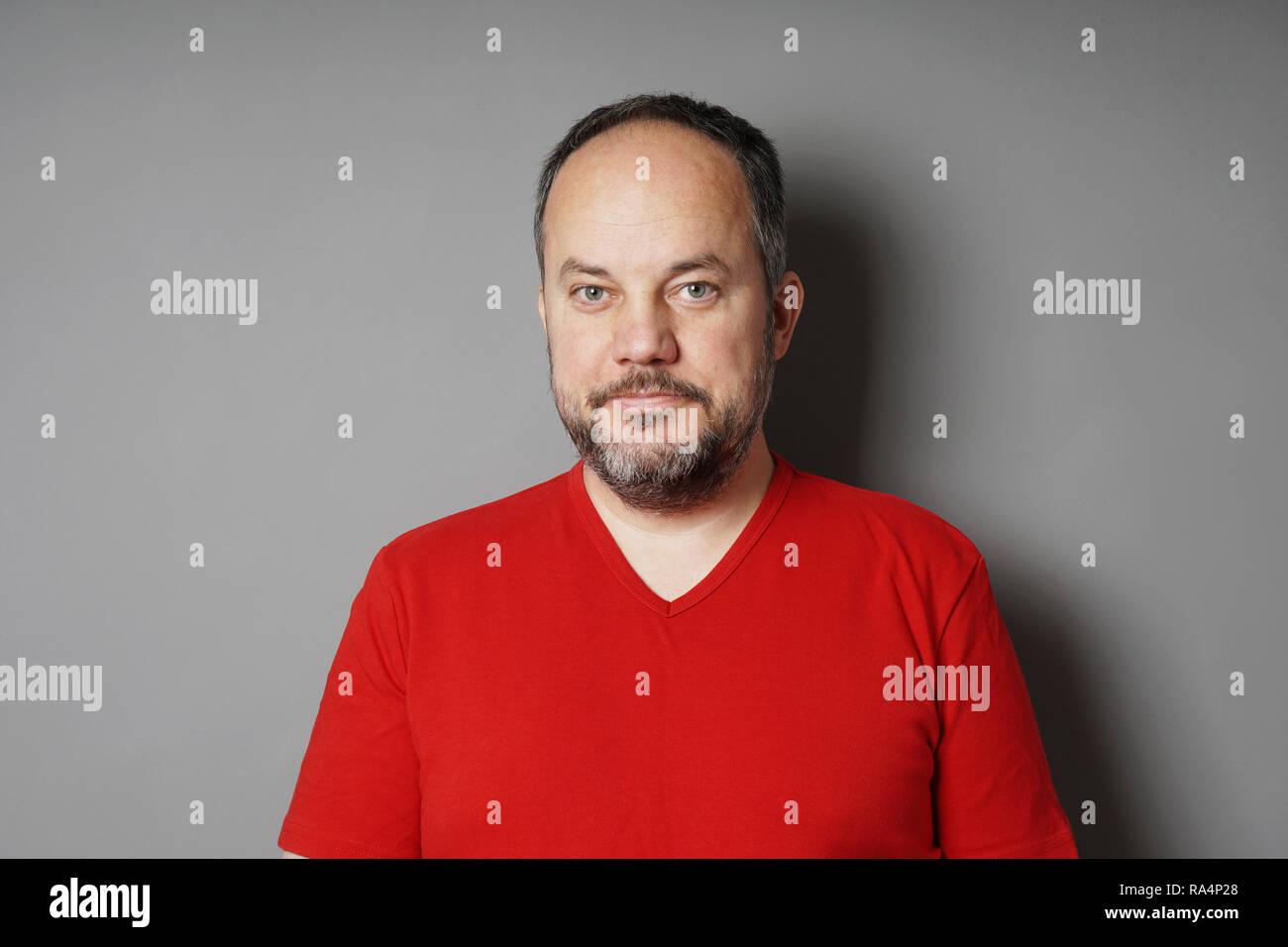 Un varón de mediana edad en su 40s vistiendo camiseta roja con pelo corto moreno y encanecimiento barba smirking - pared gris fondo con espacio de copia Imagen De Stock