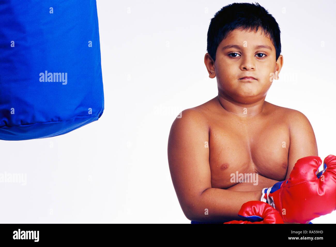 Retrato de un joven boxeador con BOXIN GUANTES Y Saco de boxeo, sudando después de un partido Imagen De Stock