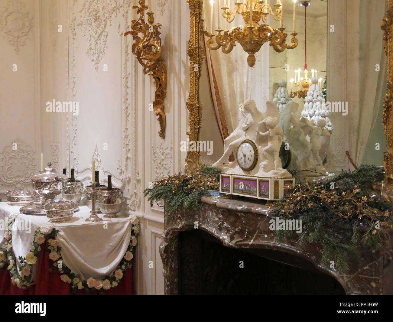 Un reloj ornamental, candelabros, espejos y mantlepiece ...