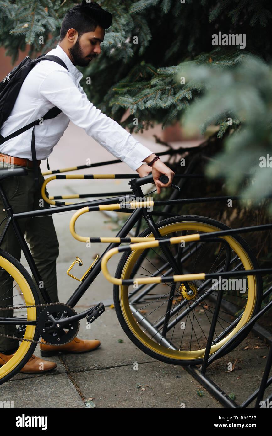 Negocios, estilo de vida, el transporte y el concepto de la gente joven - hombre indio de aparcamiento en la calle Ciudad de bicicletas Foto de stock