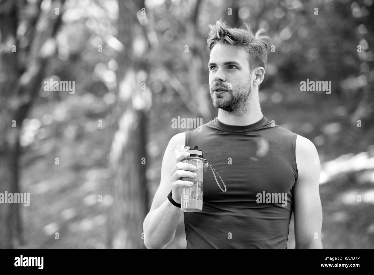 A sólo un minuto de descanso. El hombre tiene apariencia atlética botella con agua. Hombre atleta en ropa deportiva se preocupa por el equilibrio hídrico. Deporte y vida sana. Atleta beber agua después del entrenamiento en el parque. Imagen De Stock