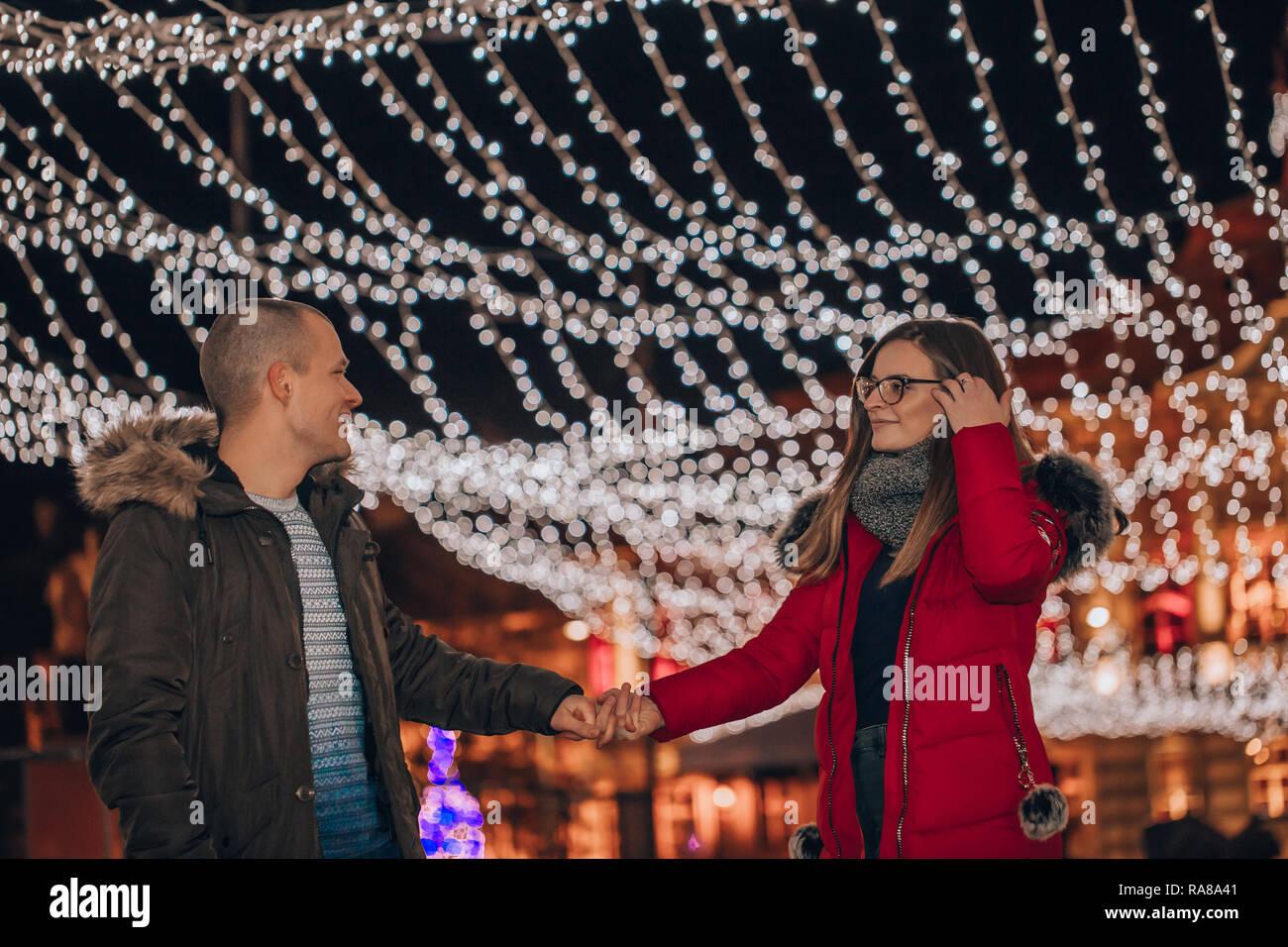 Pareja joven en ropa de invierno en la calle de la ciudad tomados de la mano en la noche durante vacaciones de invierno. Decoración luminosa - Imagen de fondo Imagen De Stock