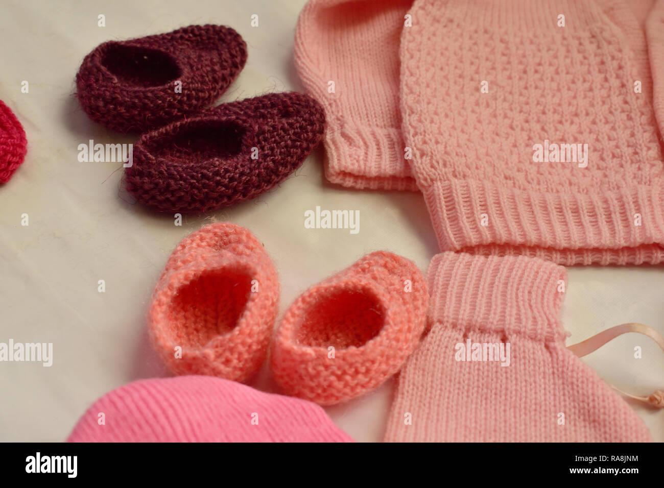 Hermosos tejidos de lana zapatos para bebés pequeños pies y rosa vestido de  bebe Imagen De e9f52bb68d5