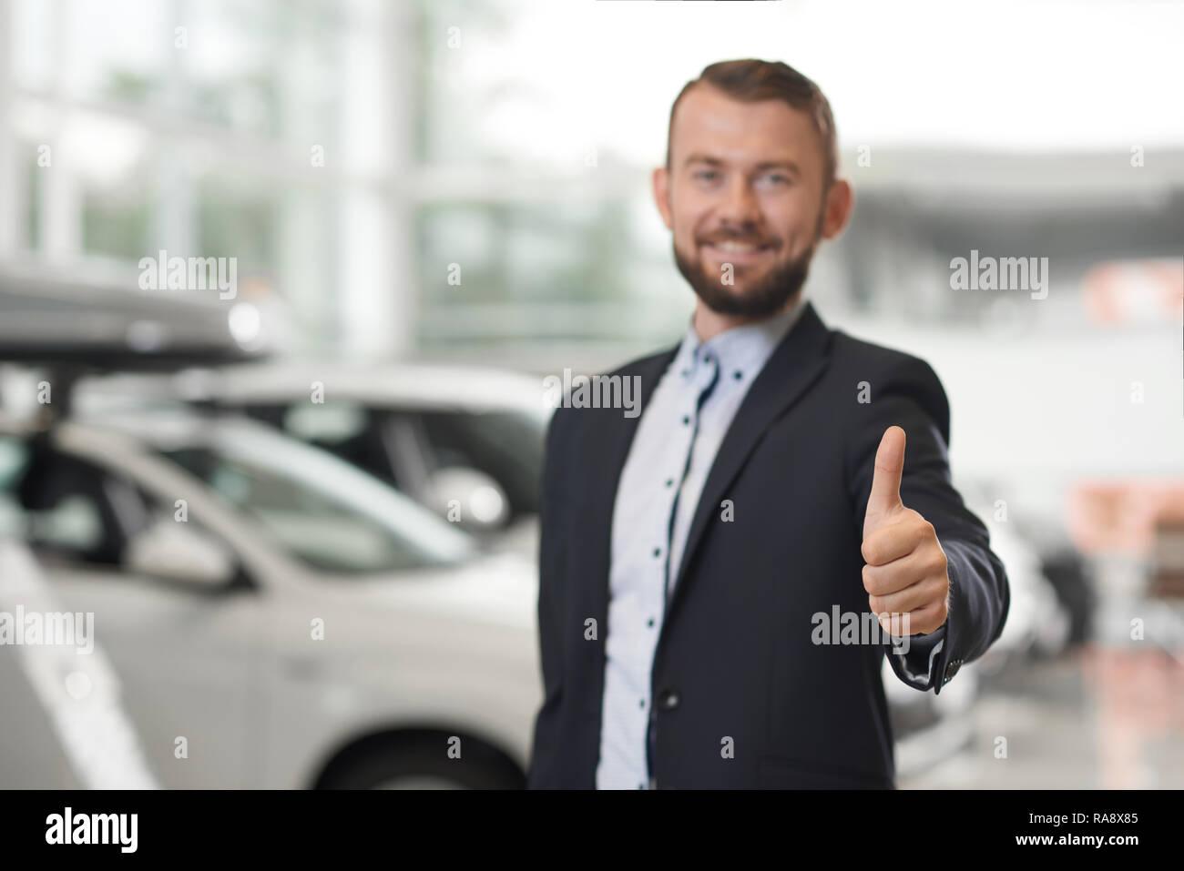 Cerca de un concesionario de coches mostrando el pulgar hacia arriba. Apuesto hombre barbado vistiendo de traje azul oscuro y camisa oficial. Manager mirando a la cámara, sonriendo mientras está de pie cerca de la fila de vehículos en el concesionario de coches. Imagen De Stock