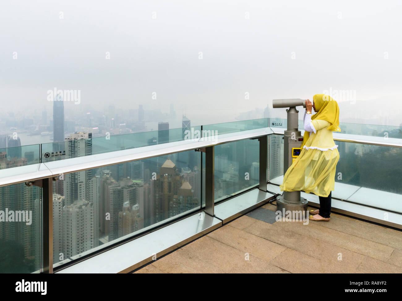 Mujer mira a través de un telescopio en la terraza de la torre Peak plataforma de visualización limitada por la bruma de la contaminación del aire, Hong Kong Imagen De Stock