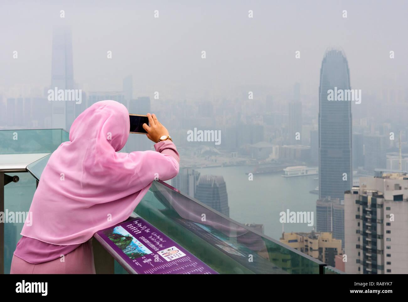 Mujer toma una foto del teléfono móvil en la cubierta de la plataforma de visualización Peak Tower restringido por la neblina de la polución del aire, Hong Kong Imagen De Stock