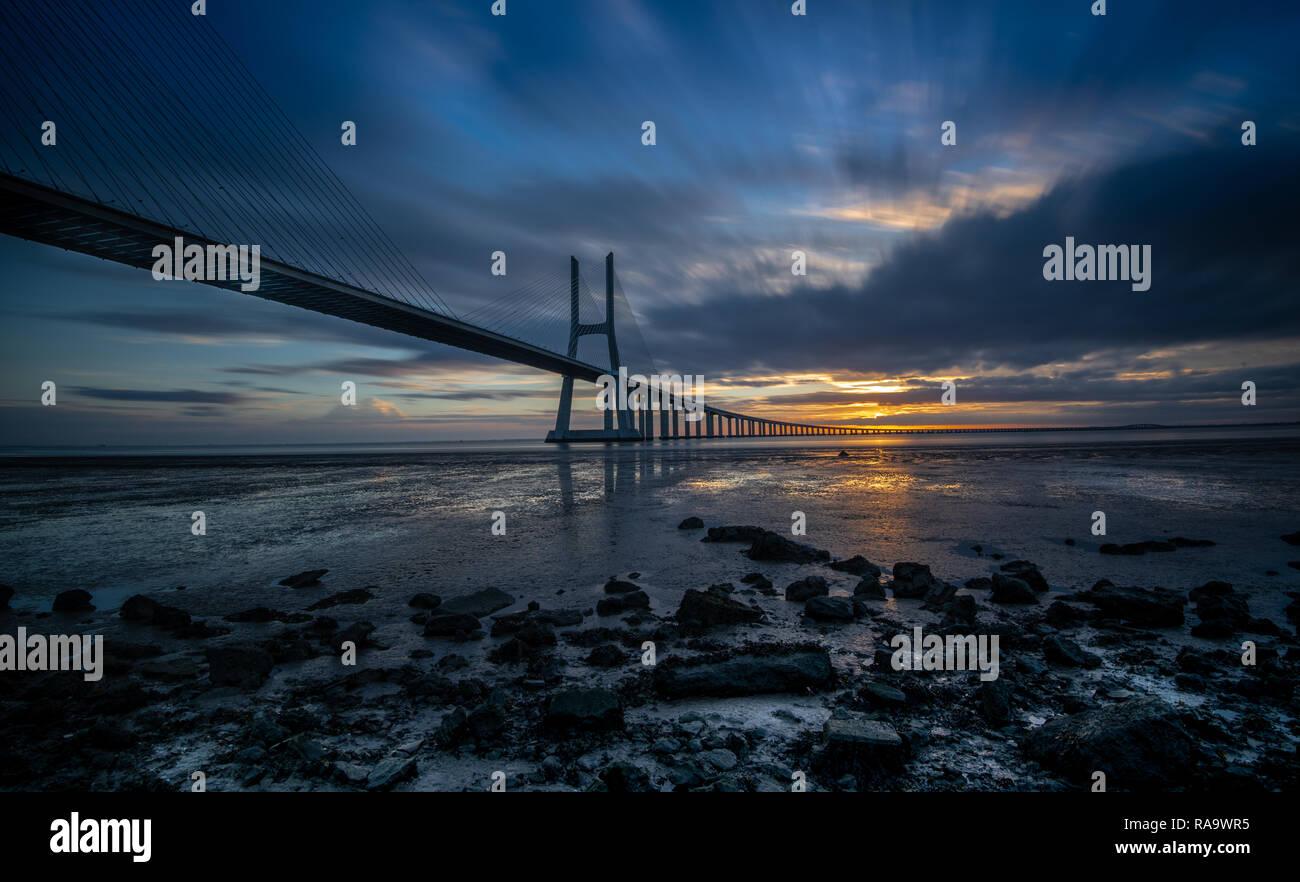El puente Vasco da Gama en Lisboa durante el amanecer. Es el puente más largo de Europa. Mide más de 10 millas (17 km) de largo y conecta el norther Foto de stock