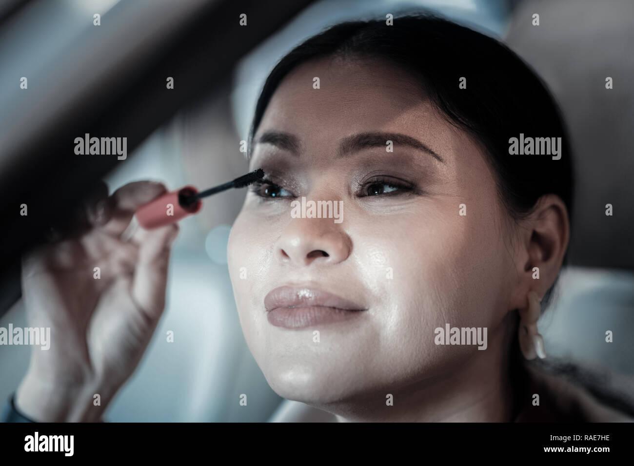 La empresaria tardíos para trabajar usando su mascara en coche Imagen De Stock