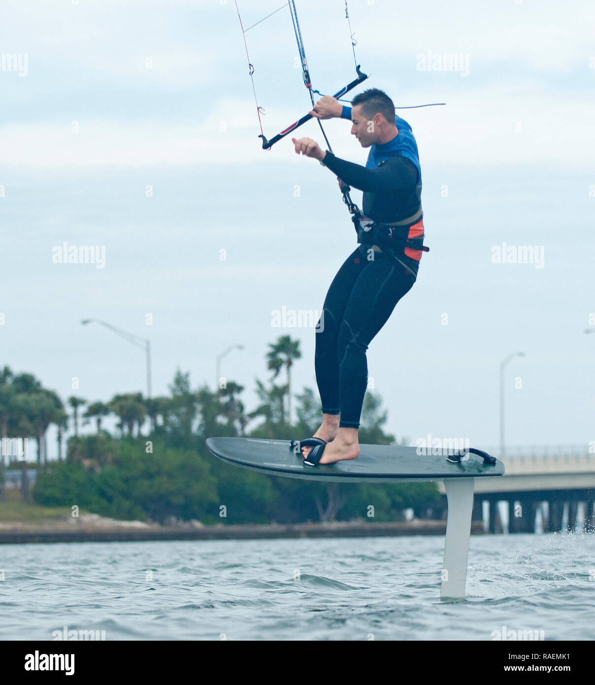 Macho de equitación kitesurfer hydrofoil y mostrando gran habilidad y atletismo Imagen De Stock