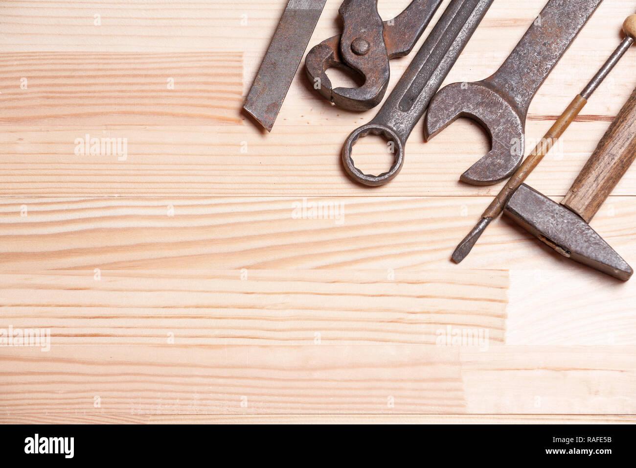 Rusty robustas herramientas industriales de trabajo antigua llave destornillador luz natural de fondo de madera Foto de stock