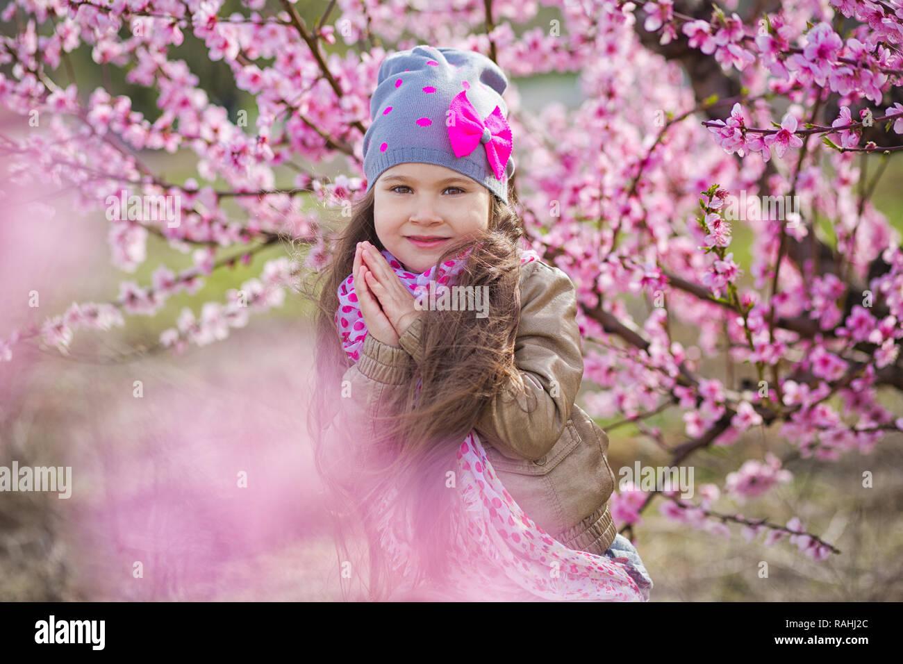 3e3e168a1 Lindo vestido elegante y hermosa chica rubia de pie en un campo de la  primavera joven con flores rosas Peach Tree.sonriente niña vestidos en rosa  en ...