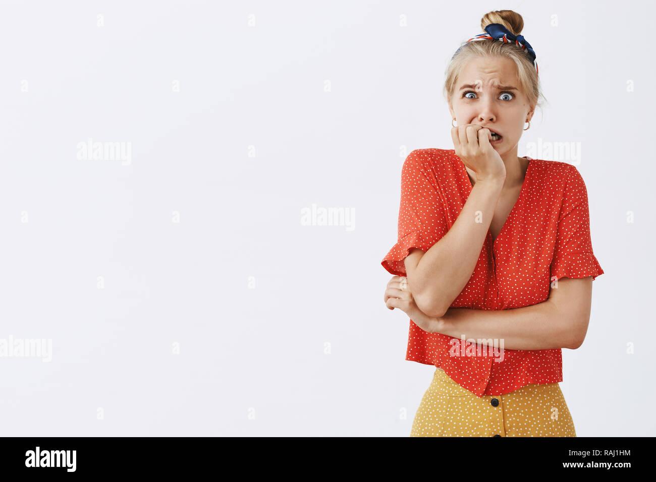 Foto de estudio de miedo mujer nervioso acerca al pánico de pie en vintage blusa punteado mordiendo las uñas y mirando interesados y preocupados en la cámara sentirse ansioso sobre fondo gris Imagen De Stock