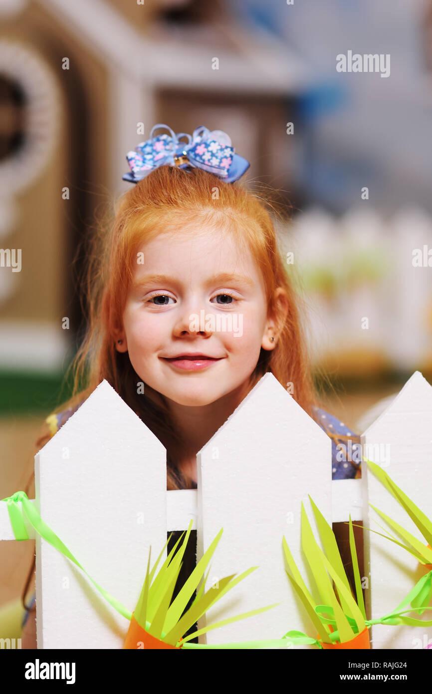 Funny Baby hermosa chica con el pelo rojo sonriente y gesticulaciones Imagen De Stock