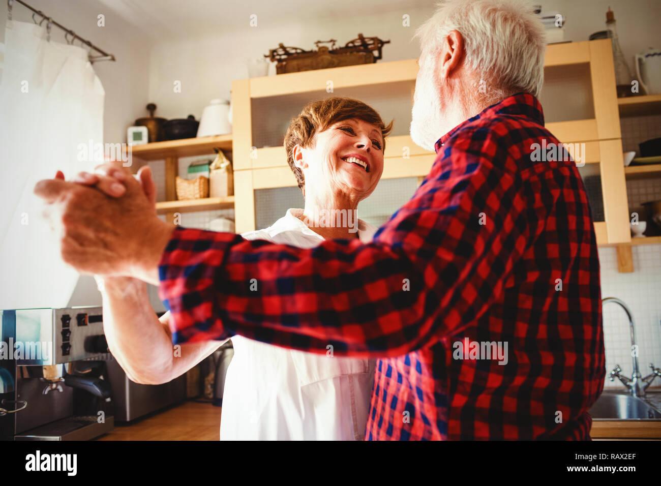 Senior pareja bailando juntos en la cocina Foto de stock