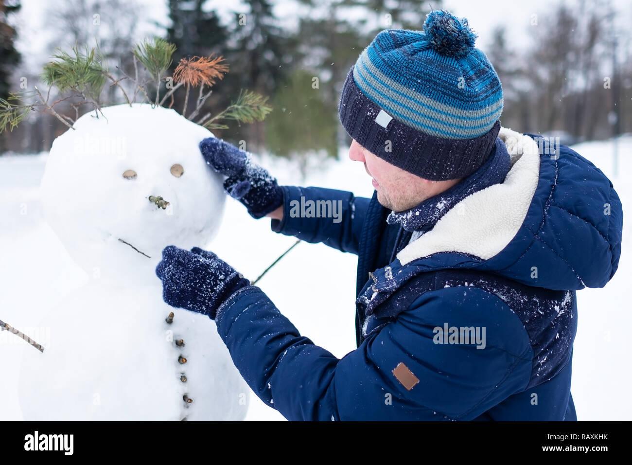 Los Jóvenes Europeos Hombre En Ropa De Abrigo Haciendo El Muñeco De Nieve De La Nieve En El Exterior Divirtiéndose Como Un Niño En Vacaciones De Invierno Fotografía De Stock Alamy