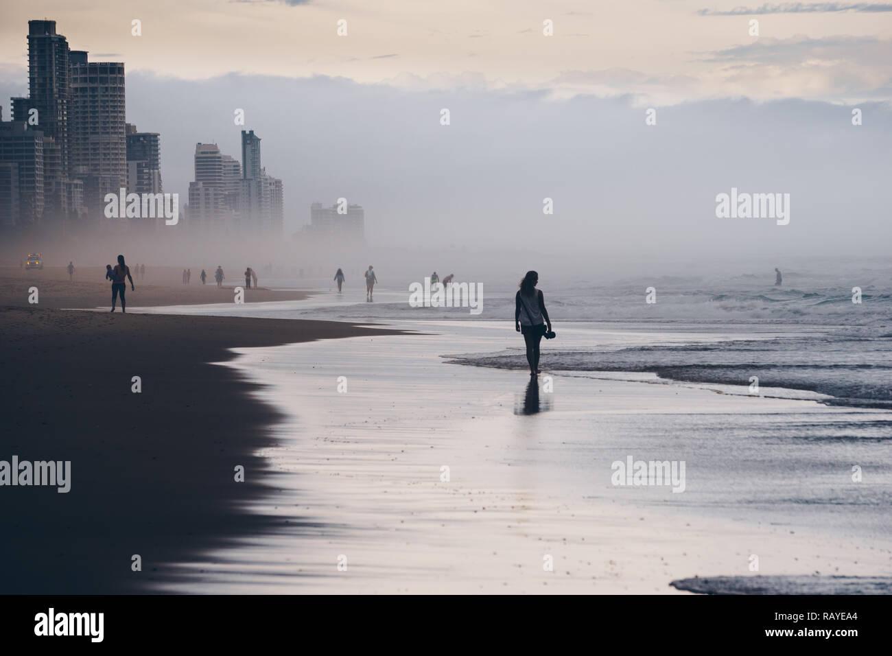 Clásica escena de verano en la playa de Surfers Paradise, con pueblos siluetas caminar y jugar. Hermosa noche de verano australiano. Foto de stock