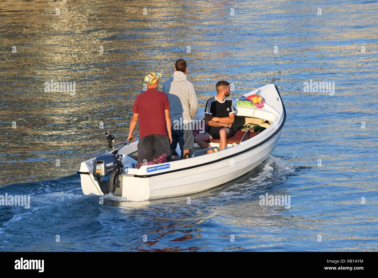 Las personas que toman un viaje de noche sobre el río en verano en el Reino Unido, en un pequeño bote con motor fuera de borda. Imagen De Stock