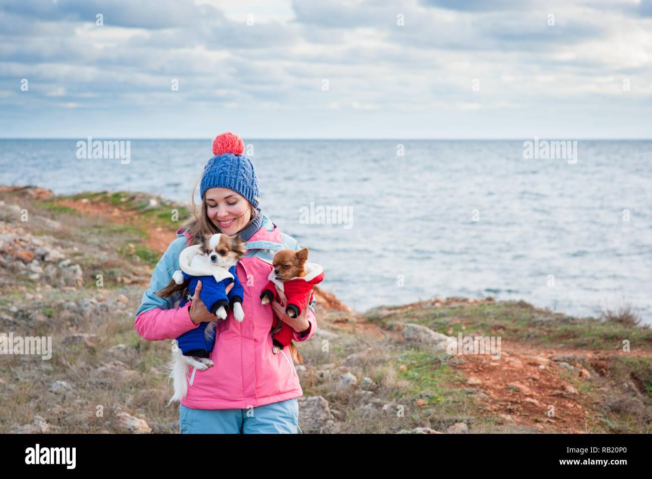 3fcc66f70316 Feliz sonrisa encantadora guapa joven femenino en el gorro de lana y pista  de traje sosteniendo