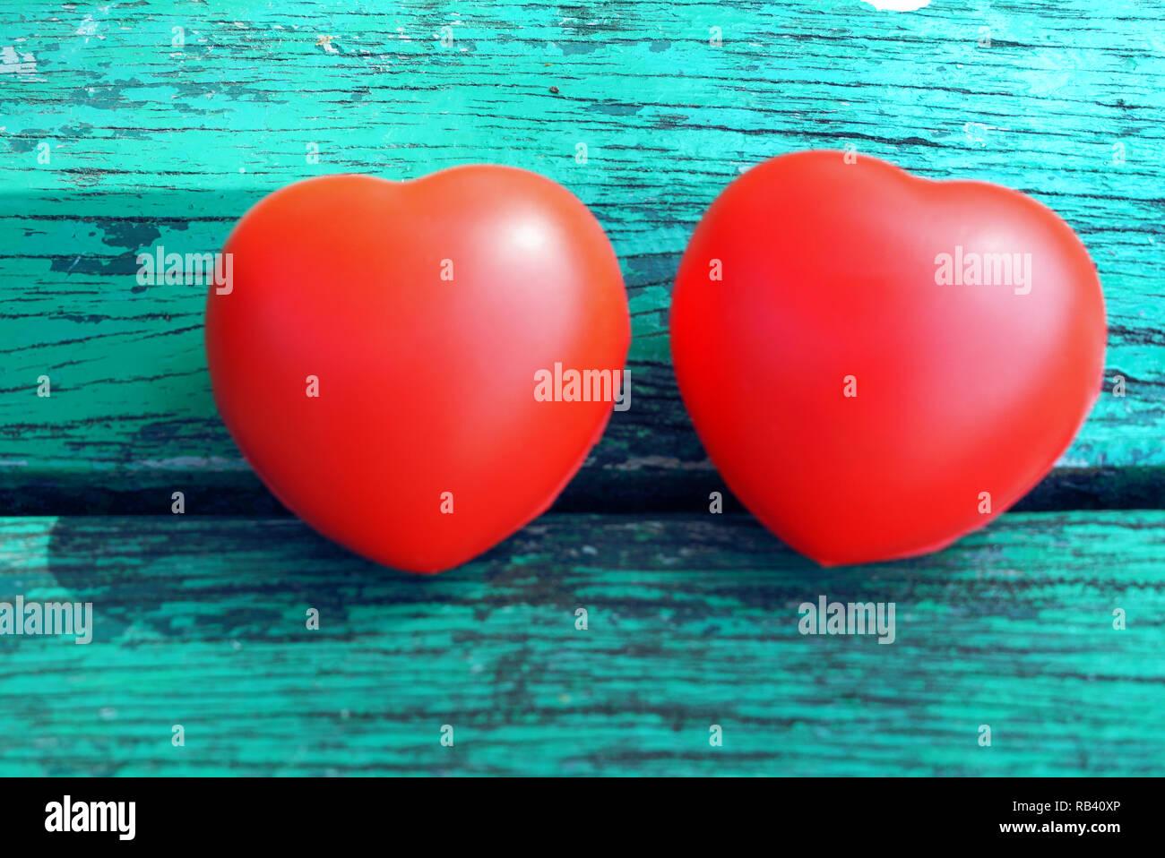 Dos corazones rojos sobre la antigua mesa verde Imagen De Stock
