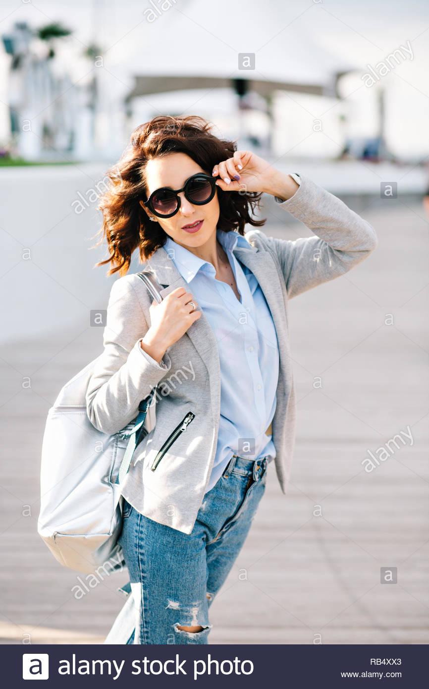 7bfce2f2a Bonita morena chica con el cabello corto es caminar en la ciudad. Viste  jeans, camisa, chaqueta y bolso. Ella toca gafas de sol en la cara y mira a  la ...