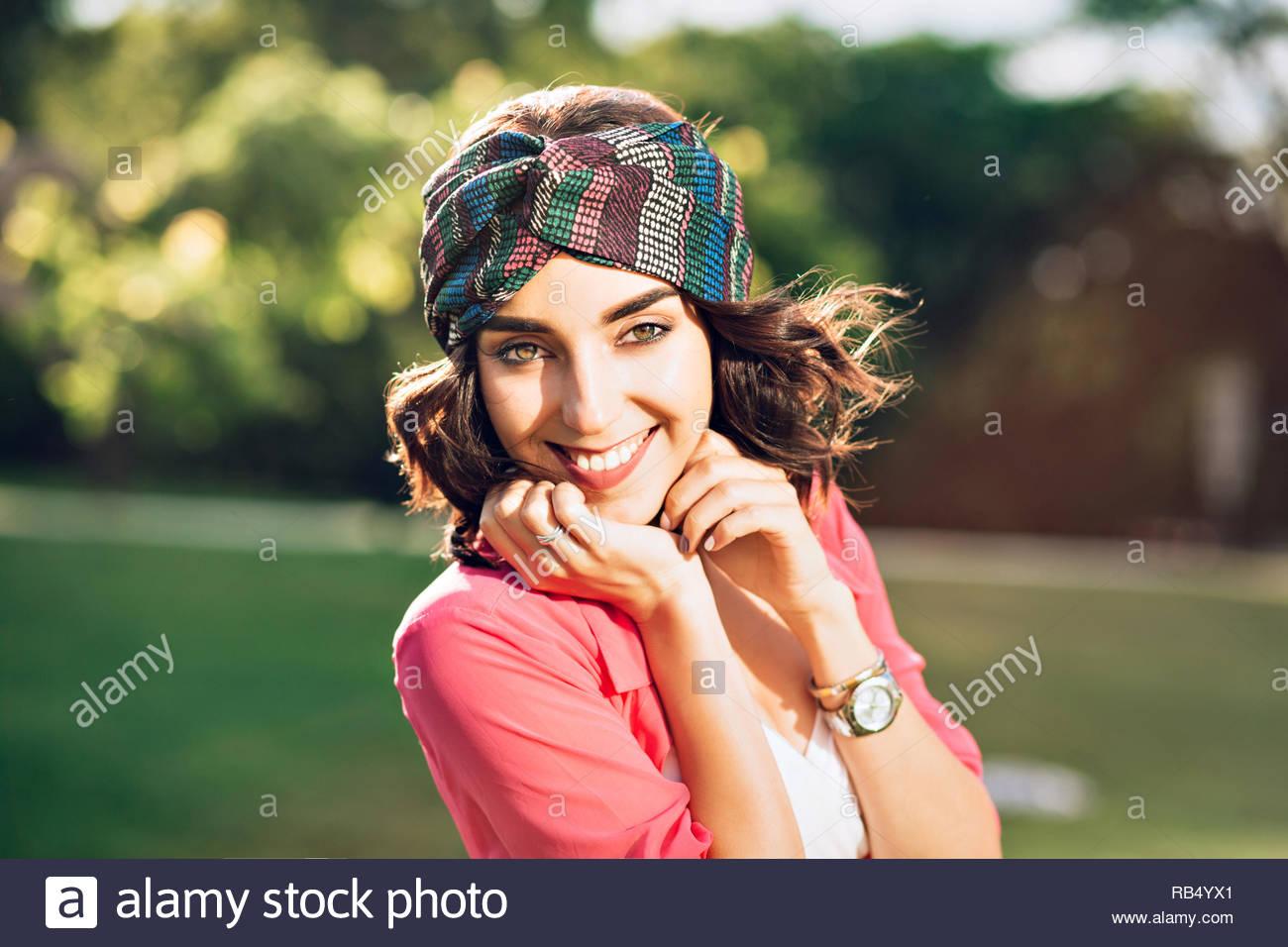 aed7bff4c2 Closeup retrato de niña morena feliz en bandana en estacionamiento. Viste  camisa rosa y sonriendo