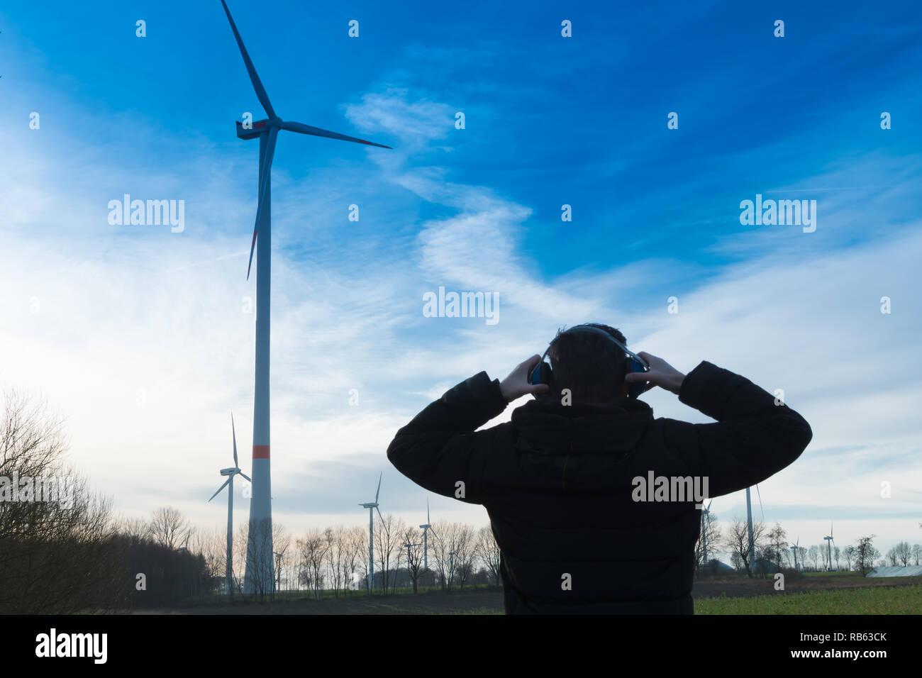 Hombre enfrente de un parque eólico utiliza protector de ruido para reducir el ruido de la turbina eólica Imagen De Stock