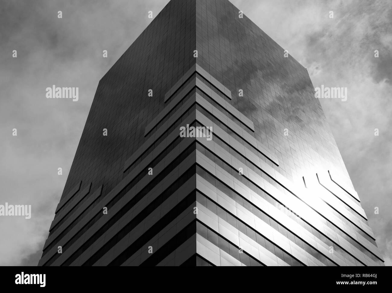 Construcción de un espejo visto desde abajo que refleja el cielo, en blanco y negro. Foto de stock
