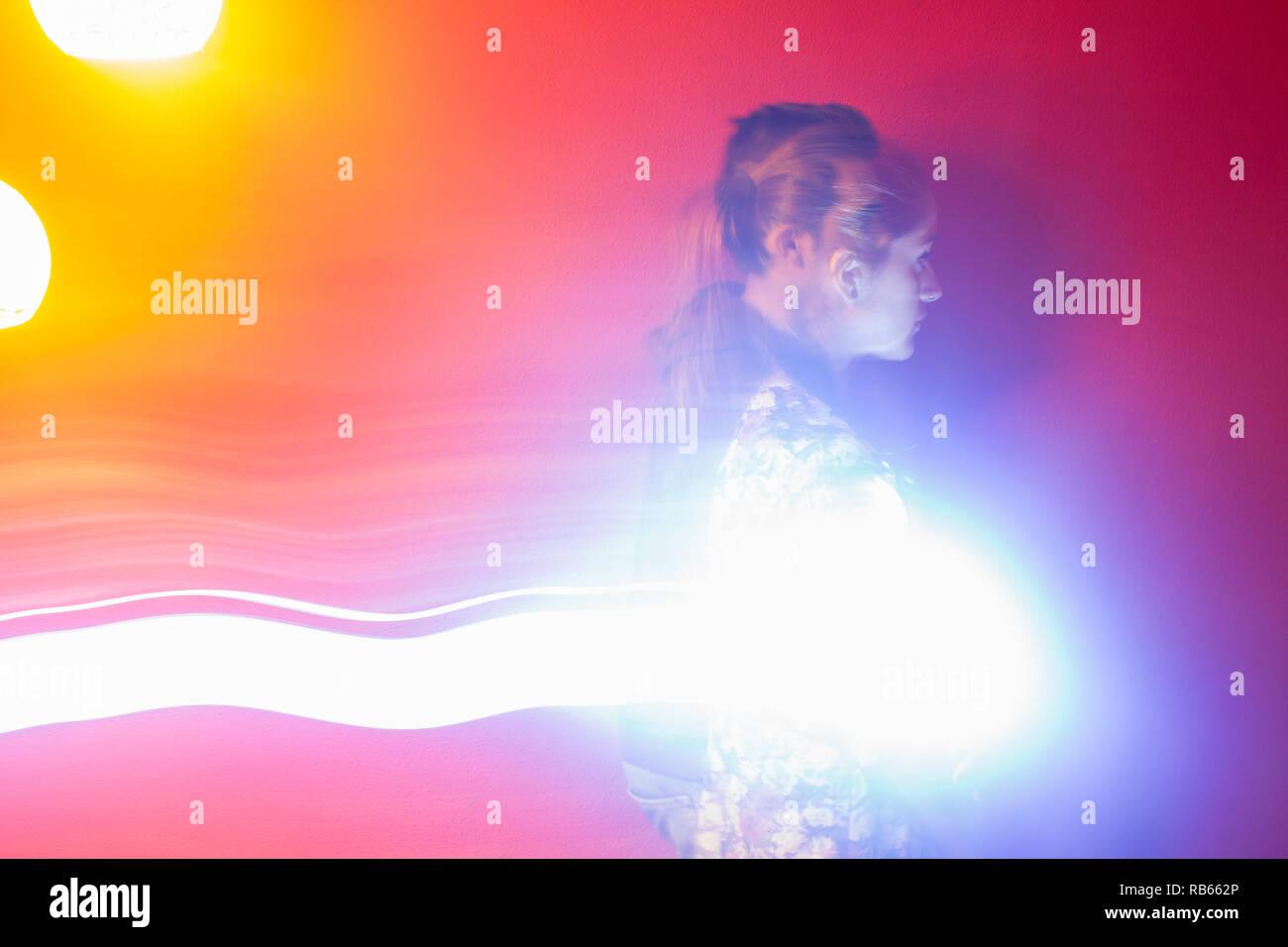 Un par de jóvenes mujeres y hombres con transparencia, fondo rojo y luces brillantes Imagen De Stock