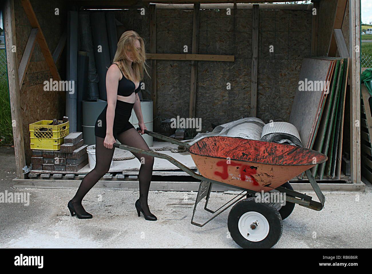 Mujer Rubia Vistiendo Nylon Medias Tacones Altos Y Pantalones Muy Cortos Empujando Una Carretilla De La Rueda Fotografia De Stock Alamy