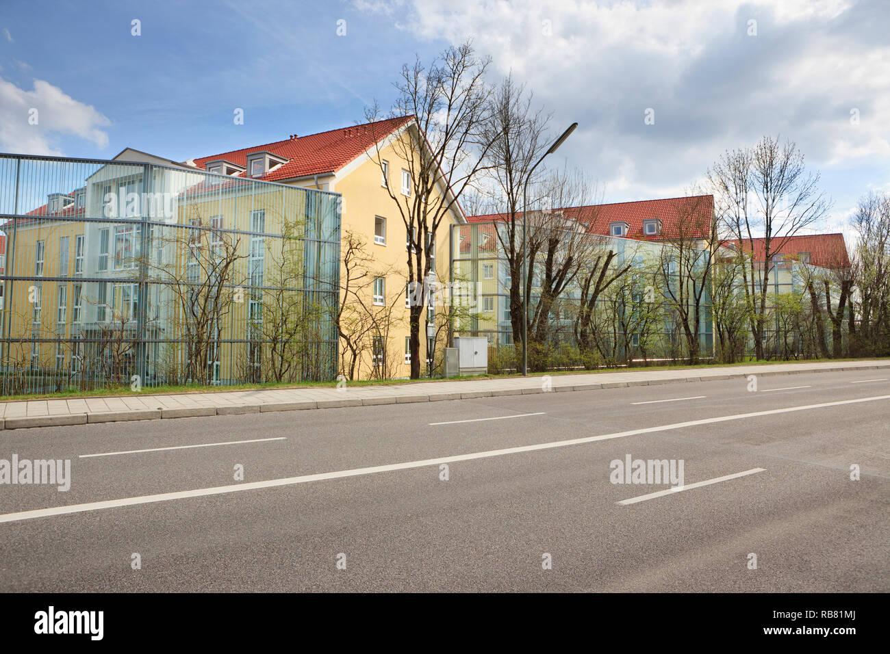 Una barrera contra el ruido de grandes paneles de vidrio protege un edificio recién construido del ruido de una carretera de cuatro carriles que pasa cerca. Imagen De Stock